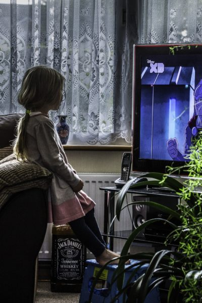 Una bambina guarda la TV in penombra